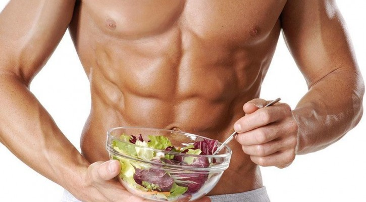 muscular man eating salad