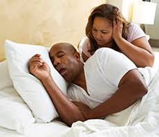 man snoring and woman covering ears
